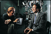 "Atsuo Takanishi of the Humanoid Research Laboratory, Waseda University, Tokyo, Japan, conversing with writer Faith D'Aluisio at his university laboratory. One of the leading researchers at Japan's Waseda University's long-term robotics project, mechanical engineer Atsuo Takanishi studied under the late Ichiro Kato, a robotics pioneer, and superb fundraiser, who made the school into the epicenter of the field. Continuing Kato's emphasis on ""biomechatronics"", replicating the functions of animals with machines, Takanishi now supervises the research group that produced WABIAN-RII (behind him in photograph). From the book Robo sapiens: Evolution of a New Species, page 18."