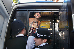 © licensed to London News Pictures. London, UK 02/08/2012. A topless FEMEN protester being arrested by police officers outside the City Hall as demonstrators wanted to protest against Islamic regimes which they claim are supported by the Olympic Committee. Photo credit: Tolga Akmen/LNP