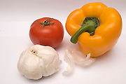 Still life with a Pepper, a tomato and garlic on white background