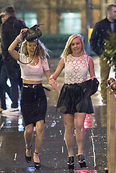 © Licensed to London News Pictures . 17/03/2013 . Manchester , UK . Two women wearing very high platform heals walk carefully on the slippery pavement . One protects her hair from the rain using her handbag . Evening revellers out in the rain and snow in to the early hours , in Manchester this St Patrick's Day morning (17th March) . Photo credit : Joel Goodman/LNP