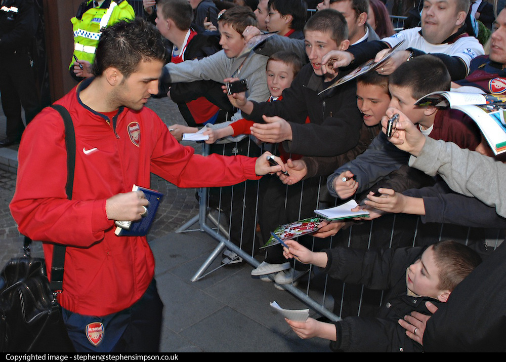 Cesc Fabregas signs autographs before boarding the bus for the Champions League game with Liverpool