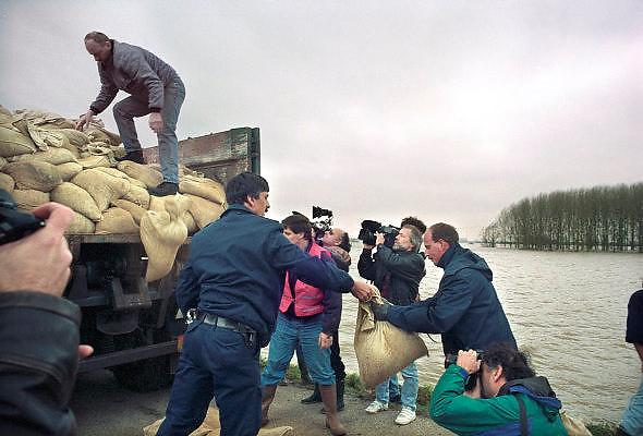 Nederland, Ooij, 01-02-1995Eind januari, begin februari 1995 steeg het water van de Rijn, Maas en Waal tot record hoogte van 16,64 m. bij Lobith. Een evacuatie van 250.000 mensen was noodzakelijk vanwege het gevaar voor dijkdoorbraak en overstroming. Op verschillende zwakke punten werd geprobeerd de dijken te versterken met zandzakken. Hier in de Ooijpolder bij Nijmegen. De gemeente had een speciale excursie per bus geregeld om de verzamelde, internationale, pers een kort kijkje op de dijk te gunnen.Late January, early February 1995 increased the water of the Rhine, Maas and Waal to a record high of 16.64 meters at Lobith. An evacuation of 250,000 people was needed because of flood risk. At several points people tried to reinforce the dikes with sandbags. Here in the Ooijpolder in Nijmegen.Foto: Flip Franssen/Hollandse Hoogte