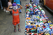 A little boy tries on a wrestler's mask before he goes in to watch the popular Mexican wrestler's dazzle the crowd an each other with wrestling antics. Mexico (Supporting image from the project Hungry Planet: What the World Eats.)