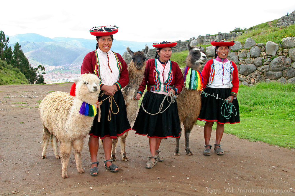 Americas, South America, Peru.  Women in traditional dress stands with llamas in the Andes.