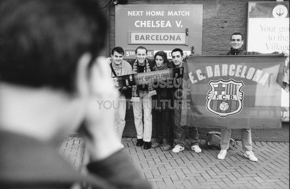 Barcelona fans holding up flags and scarves