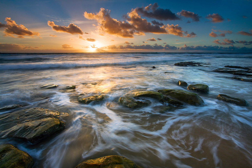 The radiance of the first minutes of sunlight cast a glow across the swirls of incoming tide and scattering of coffee rocks.