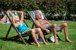 © Licensed to London News Pictures. 07/05/2018. LONDON, UK.  A couple sunbathes on the hottest May Bank Holiday on record in Regent's Park.  Photo credit: Stephen Chung/LNP