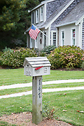 American flag flying and traditional clapboard architecture house and postbox near Cockle Cove at Chatham, Cape Cod, New England, USA
