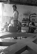 Man in workshop making a CND sign. Glastonbury.