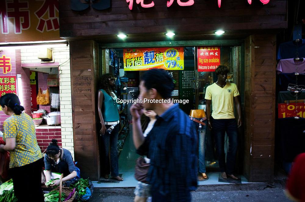 GUANGZHOU, 3. Mai , 2010:.ein Chinese geht an einem Laden mit Schwarzen Mannequins  in der Naehe des Tianxiu Kaufhauses in Guangzhou vorbei...