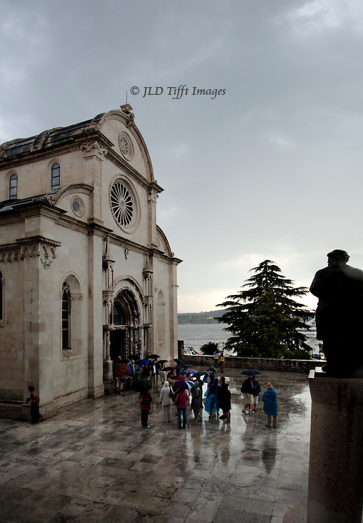 Sibenik, Cathedral of St. James, built 1431-1535.  Architects Juraj (George) of Dalmatia and Niccolo of Florence. West end exterior from plaza in a rainstorm.  Tourists huddled around the entrance.