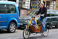 In Prenzlauerberg, the doting mom rides her bike with her child's bike in the front basket, in a not atypical scene. Berlin, Germany.