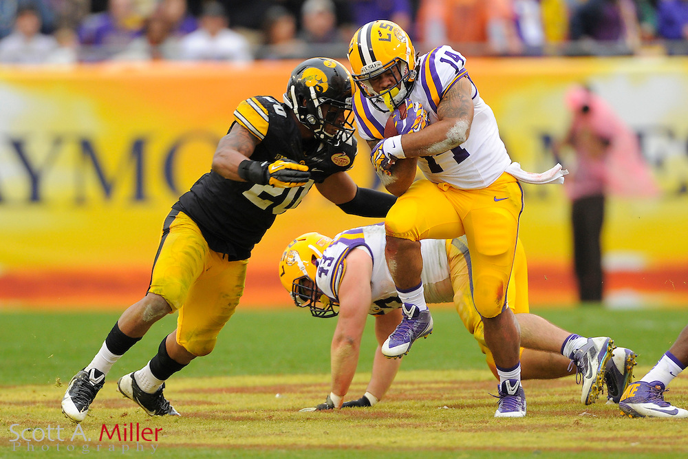 Iowa Hawkeyes linebacker Christian Kirksey (20) tackles LSU Tigers running back Terrence Magee (14) during LSU's 21-14 win in the 2014 Outback Bowl at Raymond James Stadium on Jan 1, 2014  in Tampa, Florida.            ©2014 Scott A. Miller