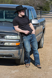 rugged cowboy leaning on a truck