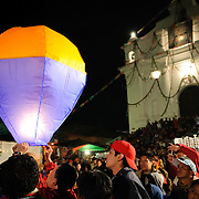 Revelers launch a paper sky lantern in the main street in front of the Church of Santo Tomas as part of a street festival before the Sunday market.. Chichicastenango is an indigenous Maya town in the Guatemalan highlands about 90 miles northwest of Guatemala City and at an elevation of nearly 6,500 feet. It is most famous for its markets on Sundays and Thursdays.