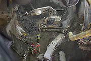 "An excavator fitted with a jackhammer has begun chipping away at the shotcrete shell separating the bottom portion or ""invert"" of the right side drift for the north cavern and the cross-cut cavern."