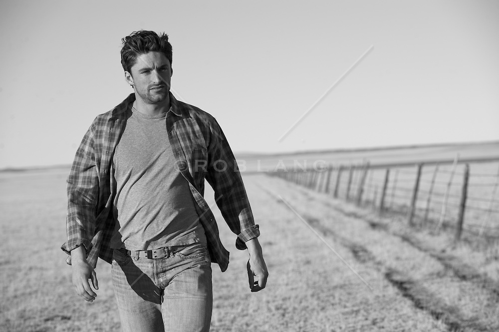 Ranch hand walking along a cattle pasture fence