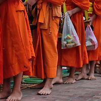 Barefoot Monks Walking at Dawn in Luang Prabang, Laos <br />