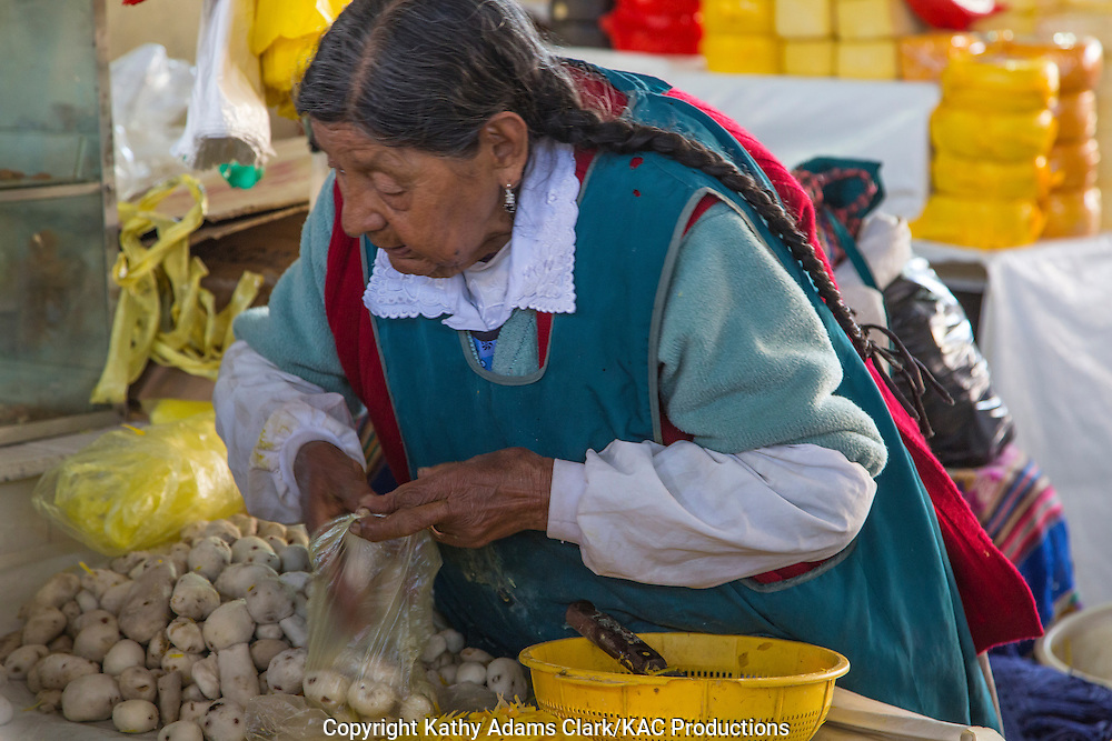 Lady in traditional dress in Cusco, Peru, bagging peeled potatos in the market.