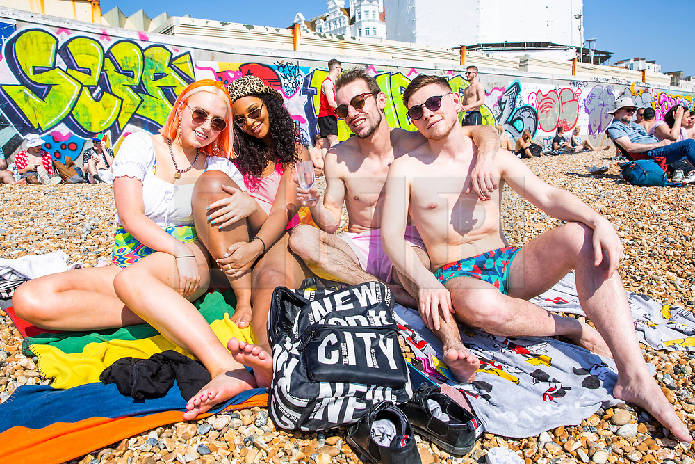 © Licensed to London News Pictures. 20/04/2019. Brighton, UK. *LtoR( NICOLE, GRACE, PEDRO and HAMISH from London join thousands of visitors and take to the beach in Brighton and Hove as sunny and hot weather is hitting the seaside resorts on the Easter Bank Holiday Saturday. Temperatures reaching 24C are the highest of the year so far. Photo credit: Hugo Michiels/LNP