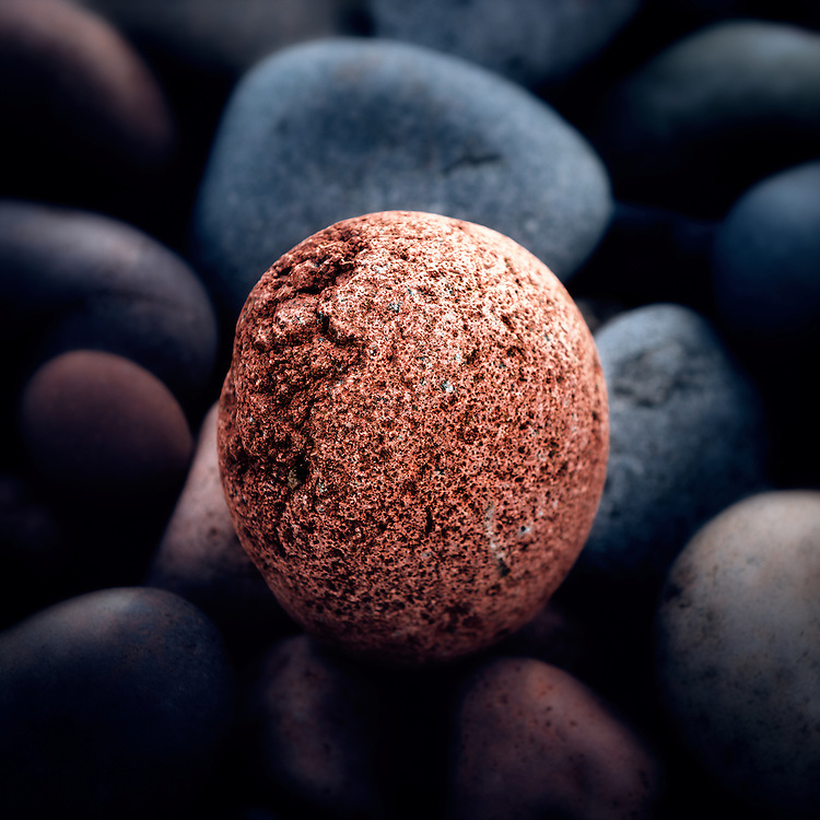 """An imperfect pink granite """"egg"""" sits among many rocks smoothed by the constant wave action on the beach at Sugarloaf Cove along the North Shore of Lake Superior in Minnesota."""