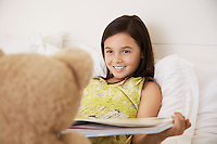 Girl reading story to teddy bear sitting on bed
