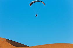 An adventure sportsman flies a powered paraglider over sand dunes near Sossusvlei, Namibia,Africa