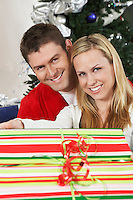 Couple holding present in front of Christmas tree