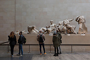 Visitors learn about the British Museum's Elgin Marbles that originate from the Parthenon in Athens, on 28th February 2017, in London, England.