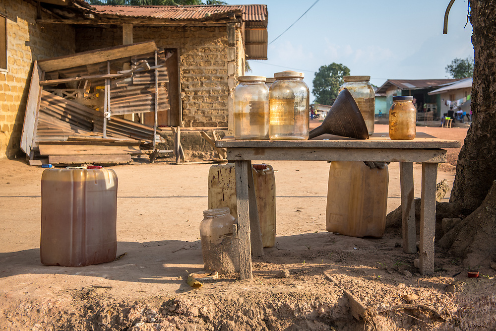 Gasoline and jars collect on a table in Ganta, Liberia