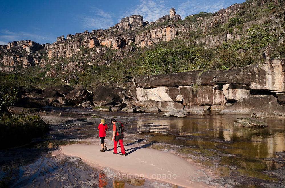 """AUYANTEPUY, VENEZUELA.  Excursionistas por el río Churum y vista de la Segunda Murralla.  El Auyantepuy es el mayor de los tepuis del Parque Nacional Canaima. En sus 700 kms2 alberga el salto angel o conocido por lengua indígena Pemon como """"Kerepacupai Vena; es la caída de agua más grande del mundo con sus 979 metros de altura. (Ramon lepage /Orinoquiaphoto/LatinContent/Getty Images)"""