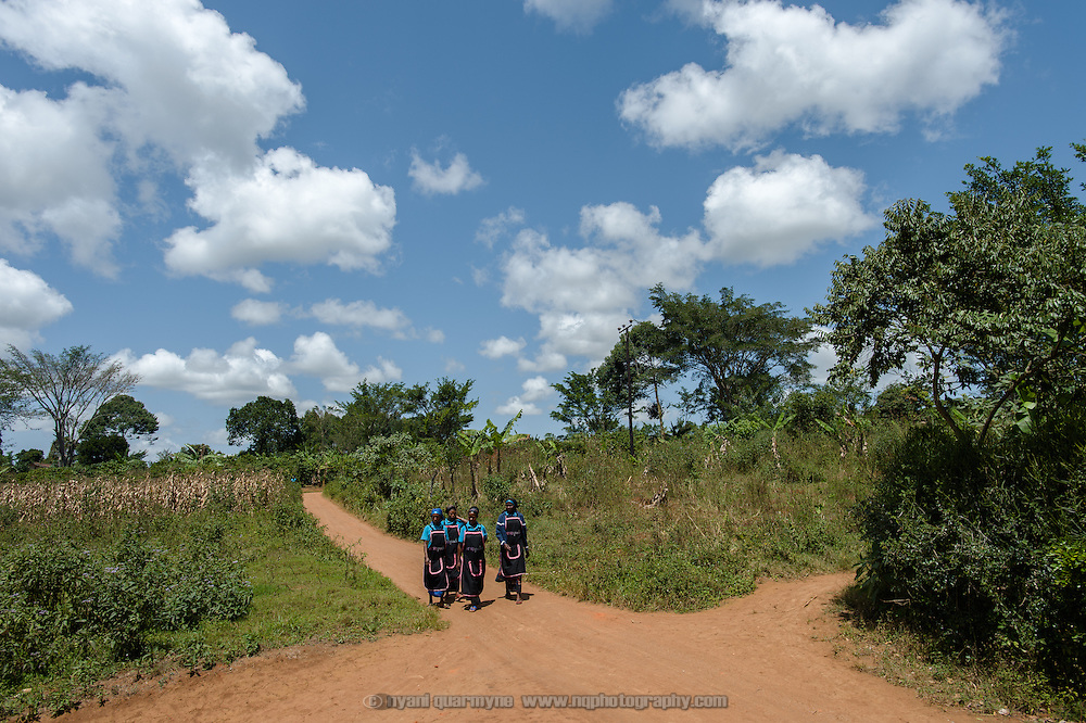 Afripads provides lunch for staff, cooked daily by a member of the community at a house near the Afripads buildings in the village of Kitengeesa in the Central Region of Uganda. Here staff members are seen walking to lunch on 30 July 2014.
