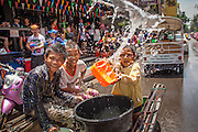 13 APRIL 2013 - BANGKOK, THAILAND:   Thai children in the back of a pickup truck throw water on tourists on Soi Nana, off of Sukhumvit Road in Bangkok. Songkran is celebrated in Thailand as the traditional New Year's Day from 13 to 16 April. The date of the festival was originally set by astrological calculation, but it is now fixed. If the days fall on a weekend, the missed days are taken on the weekdays immediately following. Songkran is in the hottest time of the year in Thailand, at the end of the dry season and provides an excuse for people to cool off in friendly water fights that take place throughout the country. Songkran has been a national holiday since 1940, when Thailand moved the first day of the year to January 1.  PHOTO BY JACK KURTZ