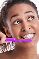 Young Mixed Race woman brushing teeth against white background