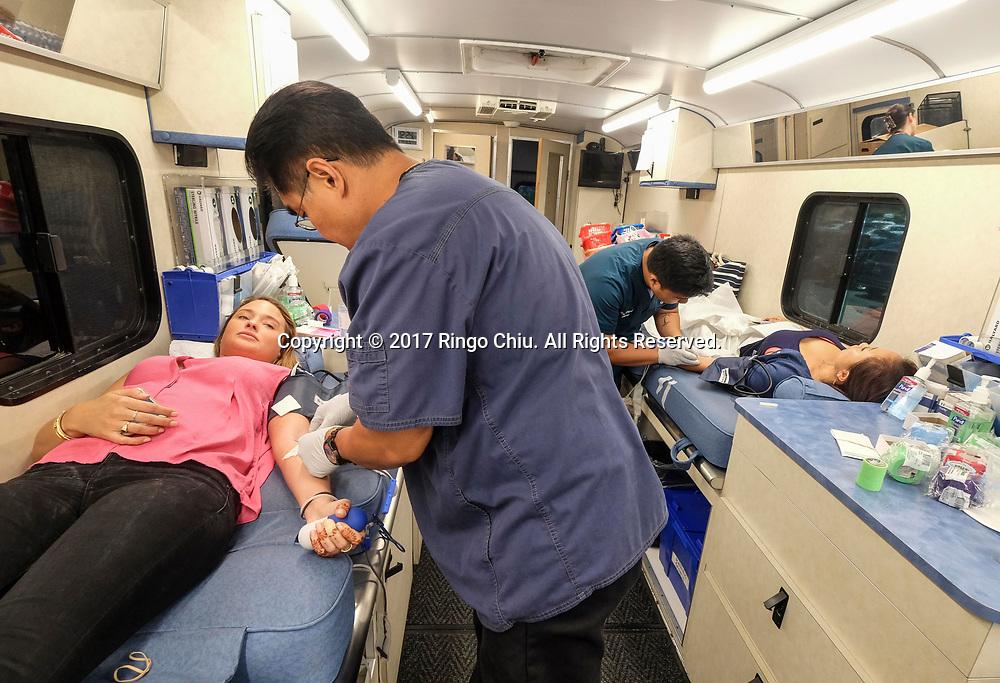 6月14日,在美国洛杉矶,雪松西奈医院的男护士为自愿献血者抽血。当日,是世界献血日,为鼓励更多的人无偿献血, 雪松西奈医院特地安排了一辆流献血车停泊在洛杉矶农民市场广场内。新华社发 (赵汉荣摄)<br /> Nurses of Cedars-Sinai Hospital draw blood from donors during the World Blood Donor Day at a Mobile Blood Drive in Los Angeles, the United States, June 14, 2017. (Xinhua/Zhao Hanrong)(Photo by Ringo Chiu)<br /> <br /> Usage Notes: This content is intended for editorial use only. For other uses, additional clearances may be required.