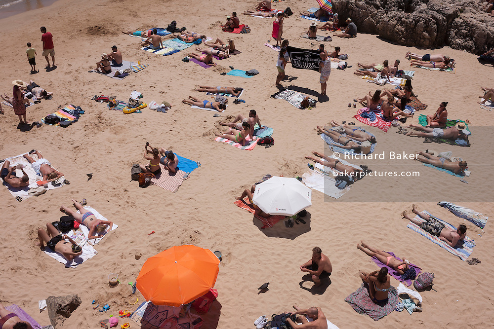 An aerial view of sunbathing individuals, couples and families, on a sandy beach cove, on 12th July 2016, at Cascais, near Lisbon, Portugal. A couple of parasols shade some, and others are topless but otherwise the crowd enjoy the fierce, mid-day heat and sunlight at this seaside resort, a short train ride west from the Portuguese capital. Cascais is a coastal town and a municipality in Portugal, 30 kilometres (19 miles) west of Lisbon. The former fishing village gained fame as a resort for Portugal's royal family in the late 19th century and early 20th century. Nowadays, it is a popular vacation spot for both Portuguese and foreign tourists and located on the Estoril Coast also known as the Portuguese Riviera. (Photo by Richard Baker / In Pictures via Getty Images)