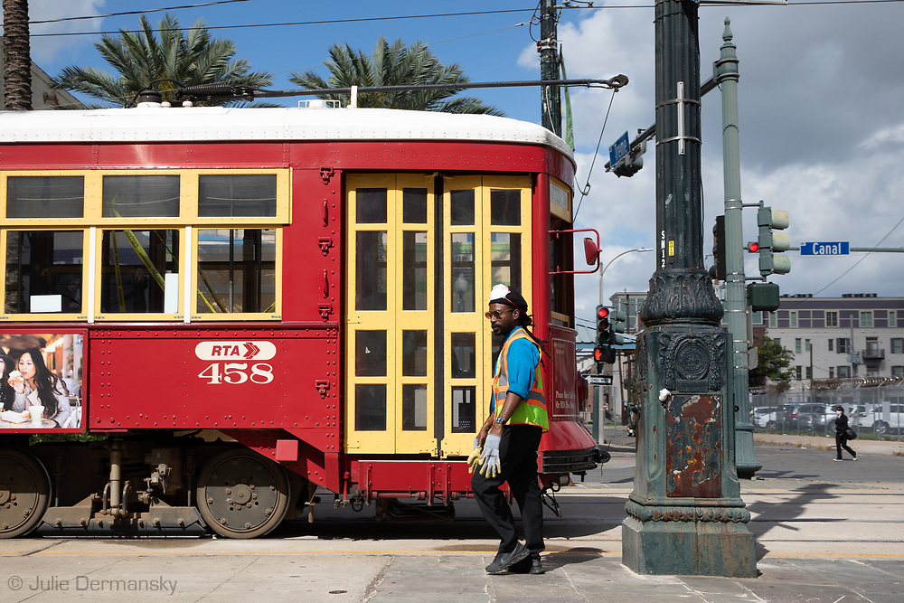 Streetcar driver with gloves and taking a break on Canal Street  in New Orleans on March 27, 2020. Tree street cars are letting people in middle entrance of the car only- the front is taped off to protect the driver. New Orleans , major city, USA