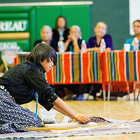 050113       Brian Leddy<br /> Chief Manuelito Daisia Curtis grinds corn as the judges look on during a performance at the Dine Language and Culture Festival Thursday in Thoreau. Awards were given out for best performances in singing, oral presentation and dancing.