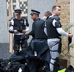 © Licensed to London News Pictures. 29/08/2011. London, UK. Police putting on riot gear  during  day 2 of the 2011 notting Hill Carnival today (29/08/2011) the second largest street festival in the world after the Rio Carnival held in Brazil . Photo credit: Ben Cawthra/LNP