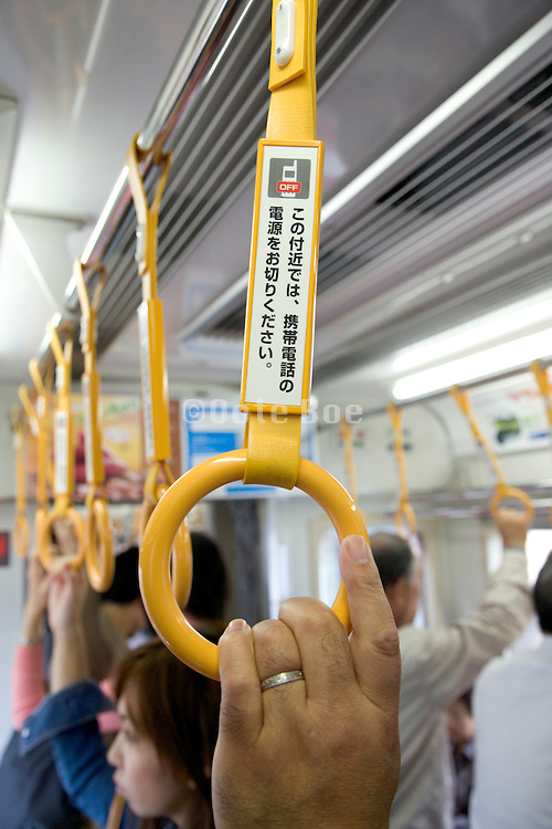 No cell phone use sign in a Japanese train passenger compartment