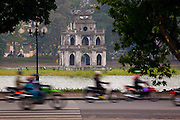 Morning motocycle traffic on a street in Hanoi, Vietnam, pass by one of the lakes in the city.