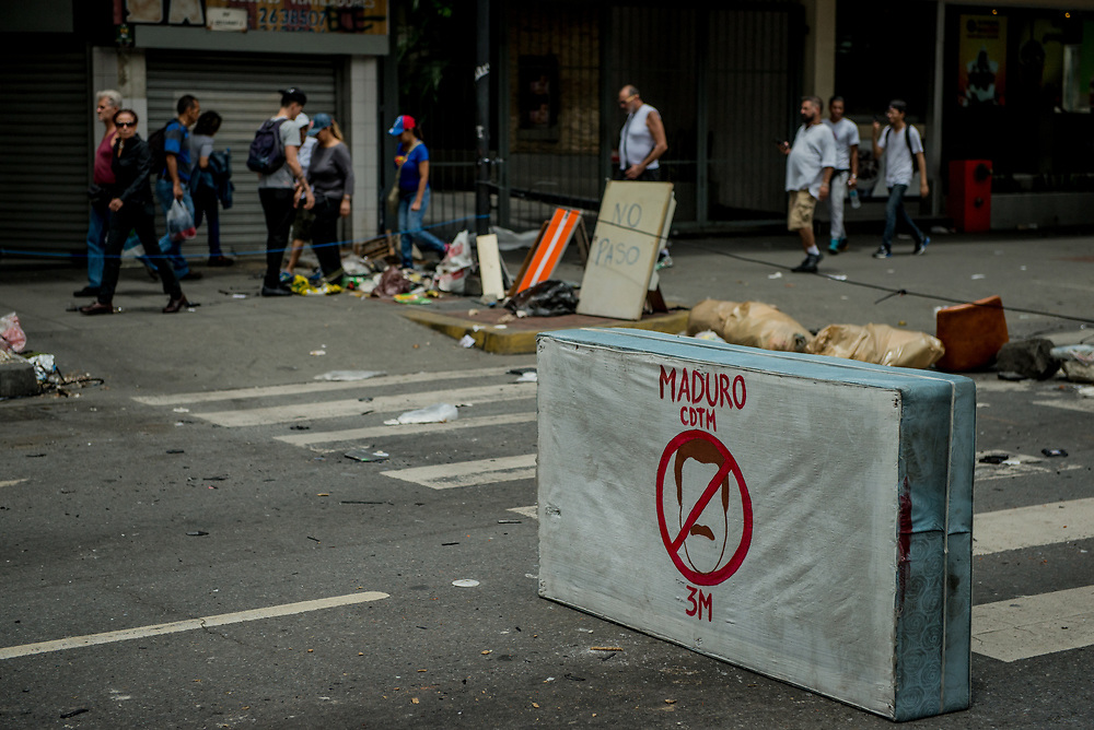 CARACAS, VENEZUELA - JULY 30, 2017:  People walk by a barricade with a mattress with an anti-President Nicholás Maduro drawing on it,  constructed by anti-government protesters who oppose today's election for a new National Constituent Assembly. Many fear that today's election for a new National Constituent Assembly will turn Venezuela similar to Cuba. Lines to vote for the new National Constituent Assembly's candidates were significantly shorter across Caracas than those of the opposition's July 16th symbolic vote against the new assembly. Nonetheless, the government reported on state television that millions had turned out to vote. Opponents of the government criticize President Maduro for calling for this election - saying the new assembly is a power grab, and will be a puppet of the President - the only candidates on the ballot are government loyalists. Critics also fear the new assembly will turn the country into a dictatorship, re-write the constitution and wipe out the democratically elected and opposition controlled congress. There have been widespread reports of voter intimidation, and of the government threatening state workers and citizens that receive government benefits like subsidized food - who report the government telling them they are obligated to vote, and if they don't, they will lose their jobs and benefits. Thousands have taken to the streets to protest the election in the days leading up to the July 30th vote.  PHOTO: Meridith Kohut for The New York Times