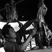 A butcher cuts meat at an early morning market in Dong Van, Ha Giang, Vietnam's northernmost province, 23 June, 2007. As cities like Hanoi and Ho Chi Minh roar with Vietnam's economic boom, Ha Giang remains a quiet, serene and beautiful mountain backwater along the Chinese border.