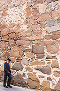 Local people strolling by ancient medieval stone wall of Palacio D'Avila in old town of Avila, Spain
