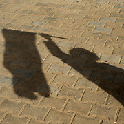 The shadow of a protestor carrying the rebellion flag is seen on the road during a protest march in central Ajdabiya.