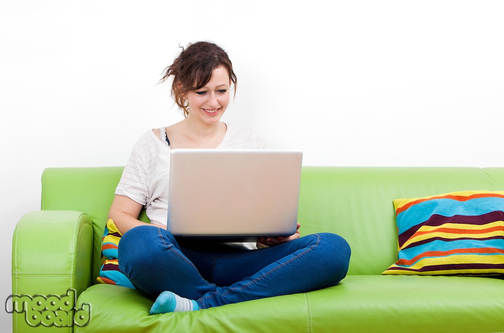 Full length of happy young woman using laptop while sitting on green sofa