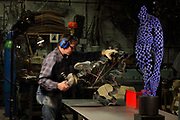 Working on a fluid steel shape for a sculpture in the Soleil Rouge workshop of Nicolas Desbons, metalworker and artist, photographed in 2017, in Montreuil, a suburb of Paris, France. On the right is Lea in Blue, a mosaic sculpture in blue steel. Desbons works mainly in steel but often in conjunction with other materials such as fibreglass, glass and clay, using both cold metal and forge techniques. He produces both figurative and abstract sculptures as well as furniture and lighting. Picture by Manuel Cohen
