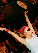 Female clubber waving her arms in the air pierced tongue, Cream, Ibiza, 2000