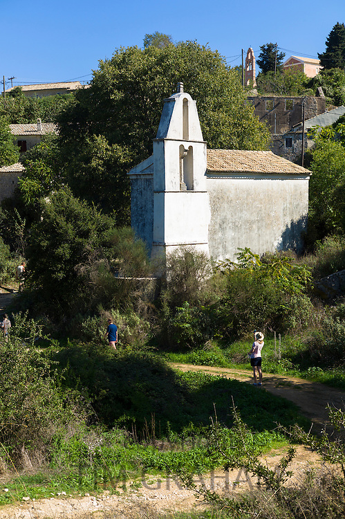 Tourists by Church of Saint Spiridon with belltower in ancient village of Old Perithia - Palea Perithea, Corfu , Greece