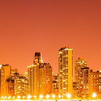 Chicago skyline at night panoramic photo with orange tones. Panorama photo ratio is 1:3 and includes the John Hancock Center building and other popular downtown Chicago city buildings. The John Hancock Center is one of the world's tallest skyscrapers and is a famous fixture in the Chicago skyline.